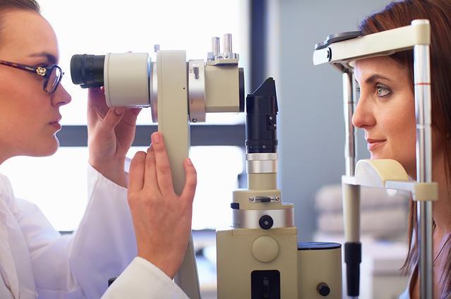 Una vista lateral de un profesional de la visión y una mujer joven mirando a través de una cámara de retina.