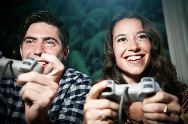 Dos adultos sosteniendo unos controles juegan video juegos