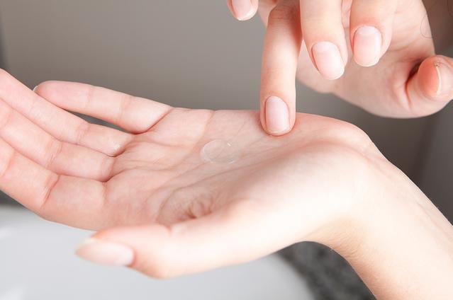 Las manos de alguien con una lente de contacto en su palma de la mano