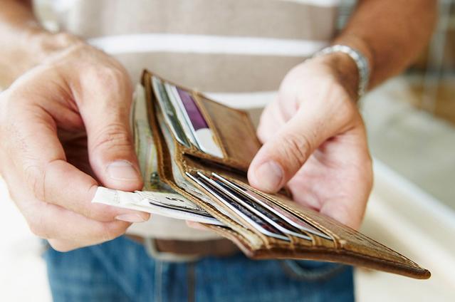 Una toma de cerca de alguien sacando facturas de una billetera