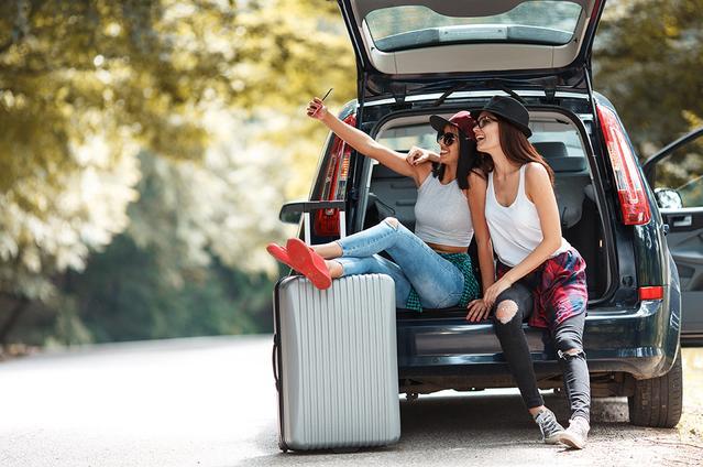 Dos chicas que sentadas en la maleta del auto en la playa, con su equipaje, están listas para viajar