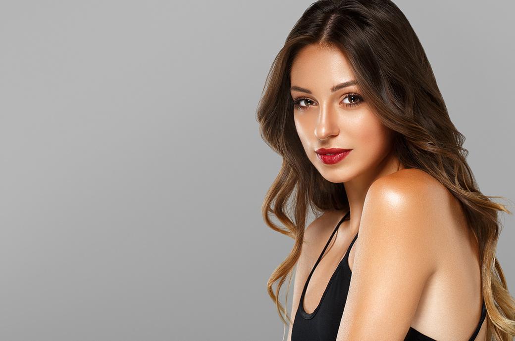 Una mujer joven y de moda posa con el hombro mirando a la cámara