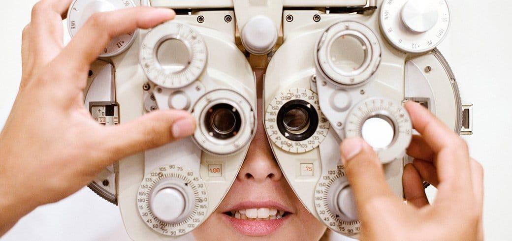 Un profesional de la visión ajusta un forópteeo mientras una mujer joven mira a través de él