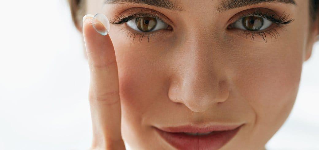 Una mujer con un lente de contacto en su dedo