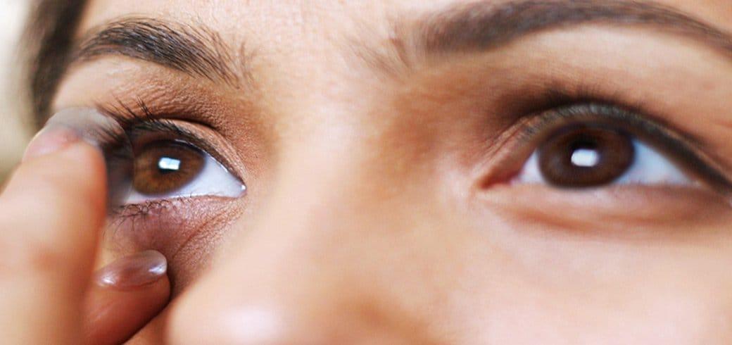 Un primer plano de una mujer joven que se mira en un espejo mientras se pone los lentes de contacto